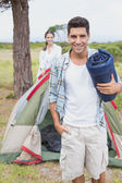 Happy couple with tent on countryside landscape — Stock Photo