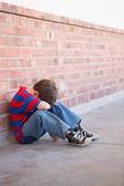 Sad pupil sitting alone in corridor — Stock Photo