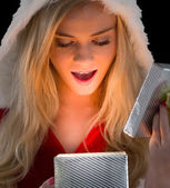 Pretty blonde in santa outfit opening gift — Stock Photo