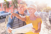 Happy tourist couple using map in the city — Foto Stock