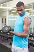 Man exercising with dumbbell in gym — Stock Photo