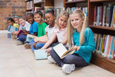 Pupils sitting on floor in library — Stock Photo