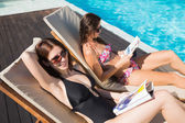 Women reading books on sun loungers by swimming pool — Stock Photo