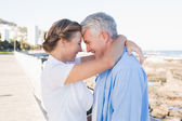 Happy casual couple hugging by the coast — Stock Photo