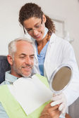 Patient admiring his new smile in the mirror — Stock Photo