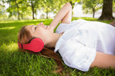 Redhead lying on grass listening to music — Foto de Stock