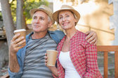 Happy mature couple drinking coffee on a bench in the city — Stock Photo