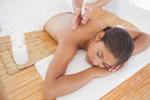 Beautiful brunette enjoying back massage — Stock Photo