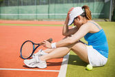 Upset tennis player sitting on court  — Stockfoto