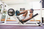Weightlifter doing leg presses in gym — Stock Photo