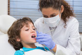 Pediatric dentist examining a little boys teeth in the dentists  — Stock Photo