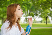 Redhead blowing bubbles in the park — Stock Photo