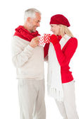 Smiling couple in winter fashion toasting with mugs — 图库照片