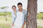 Smiling couple standing by tree trunk — Stock Photo