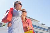 Happy senior couple holding shopping bags — Stockfoto
