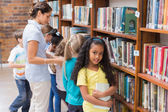 Pupils and teacher looking for books in library — Stock Photo