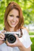 Redhead taking a photo in the park — Stockfoto