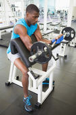 Young man lifting barbell in gym — Foto de Stock