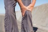 Active senior man touching his injured knee — Stock Photo