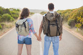 Hiking couple standing on countryside road — Stock Photo