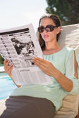 Woman reading newspaper on sun lounger by pool — Stock Photo