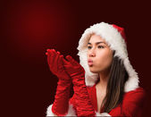 Brunette in santa outfit blowing — Stockfoto