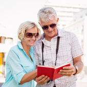 Happy tourist couple using tour guide book in the city — Стоковое фото