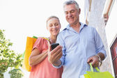 Happy senior couple looking at smartphone holding shopping bags — Stock fotografie