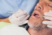 Dentist examining a patients teeth — Stok fotoğraf