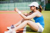 Pretty tennis player sitting on court — Stock Photo