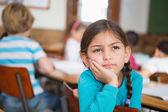Thoughtful pupil sitting at her desk — Fotografia Stock