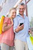 Happy senior couple looking at smartphone holding shopping bags — Stock Photo