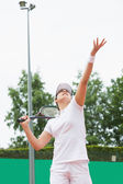 Focused tennis player serving the ball — Stock Photo
