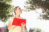 Blonde woman using her guide book — Stockfoto