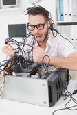 Angry computer engineer pulling wires — Stock Photo