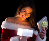 Pretty brunette in santa outfit opening gift and smiling at came — Stock Photo