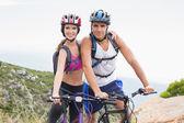 Athletic couple mountain biking — Stock Photo