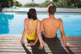 Couple sitting by swimming pool — Foto de Stock