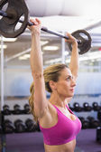 Fit young woman lifting barbell in gym — Stock Photo