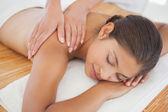 Beautiful brunette enjoying shoulder massage — Stock Photo