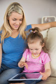 Mother and daughter using digital tablet on couch — Стоковое фото