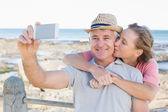 Happy casual couple taking a selfie by the coast — Stock Photo