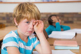 Upset pupil sitting at his desk — Foto Stock