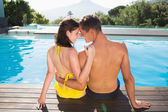 Couple sitting by swimming pool — Stock Photo
