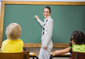 Teacher writing on chalkboard — Stock Photo