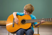 Pupil playing guitar in classroom — Стоковое фото