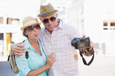 Happy tourist couple taking a selfie in the city — Stock Photo