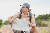 Hiking man sitting with map on mountain terrain — Stock Photo