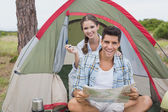 Couple with map sitting outside their tent — Stock Photo