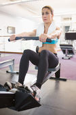 Woman working on fitness machine at gym — Stock Photo